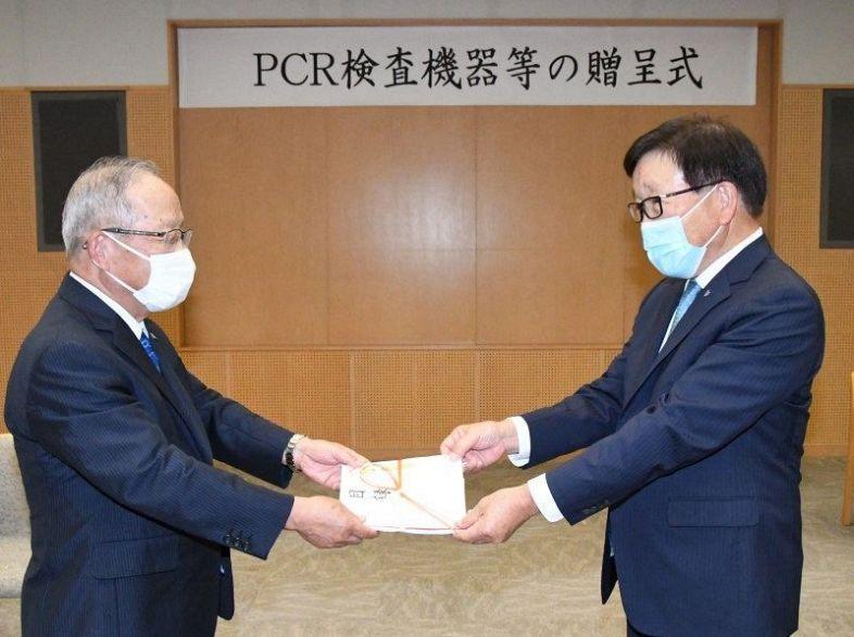 松山理事長(右)に目録を手渡す清水副会長